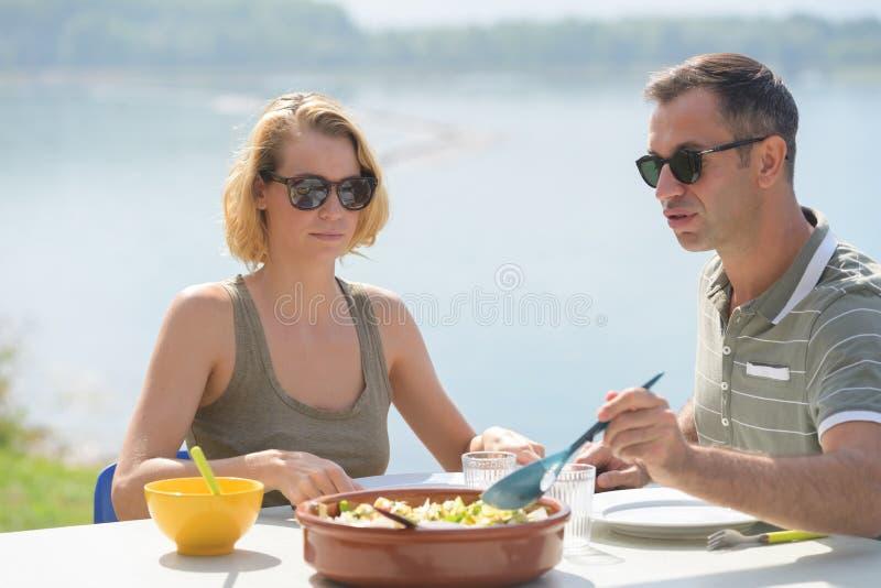 Les couples mangeant le repas dehors arrosent à l'arrière-plan image stock