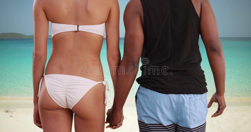 Les couples millénaires d'afro-américain tiennent des mains tout en regardant l'horizon photo libre de droits