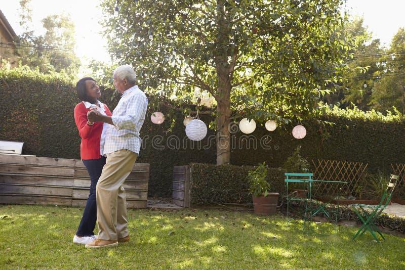 Les couples noirs supérieurs dansent dans leur jardin arrière, intégral images libres de droits