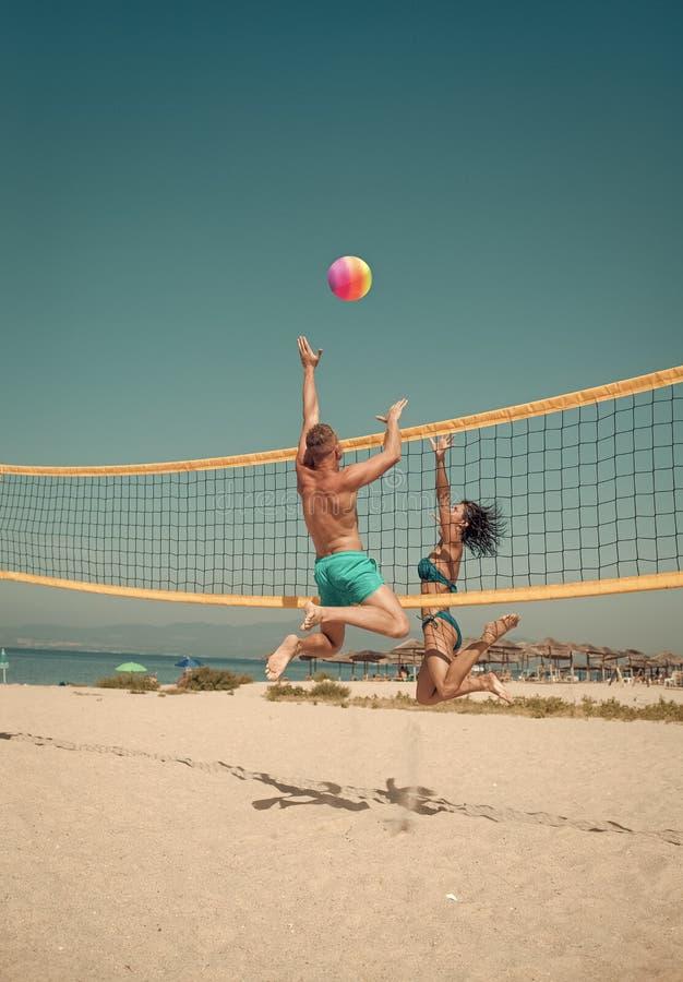 Les couples ont l'amusement jouant le volleyball Les jeunes couples actifs sportifs ont battu outre de la boule de volée, jeu de  photos libres de droits