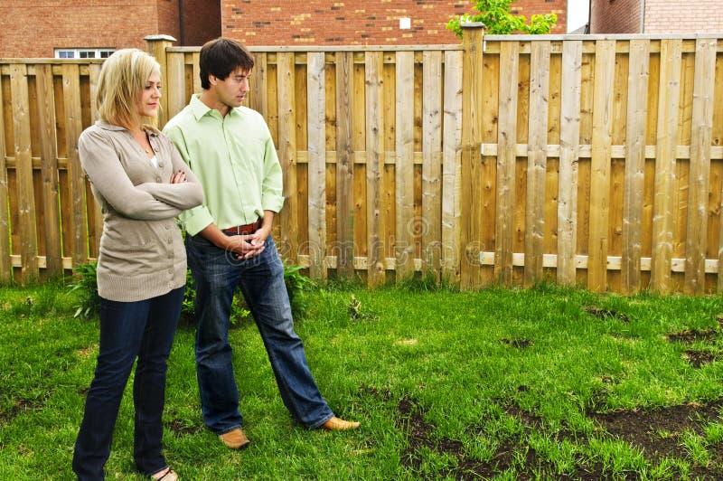 Les couples ont préoccupé par la pelouse photographie stock libre de droits