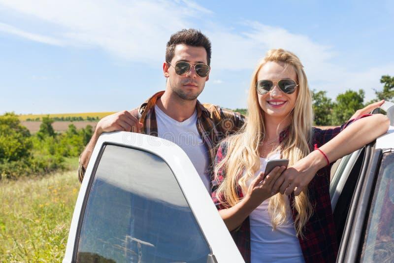 Les couples près de la femme de route de campagne de voiture tiennent le téléphone intelligent images stock