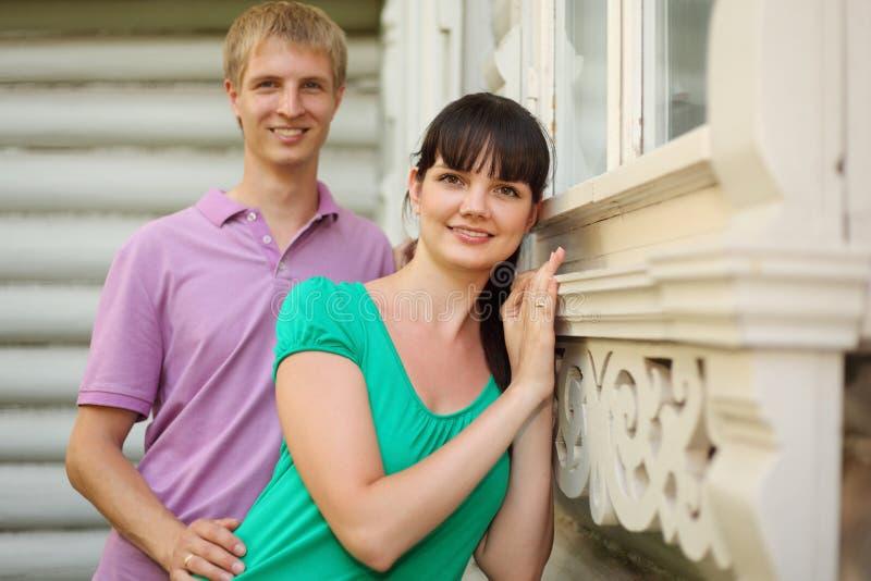 les couples restent près de la maison en bois de village image stock