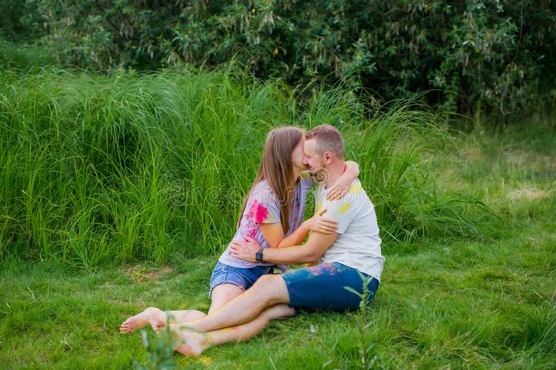 Les couples romantiques ont couvert dans le baiser de peinture dehors photo stock