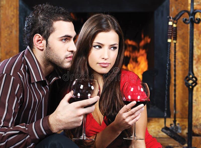 Les couples romantiques s'approchent de la cheminée et du vin photo stock