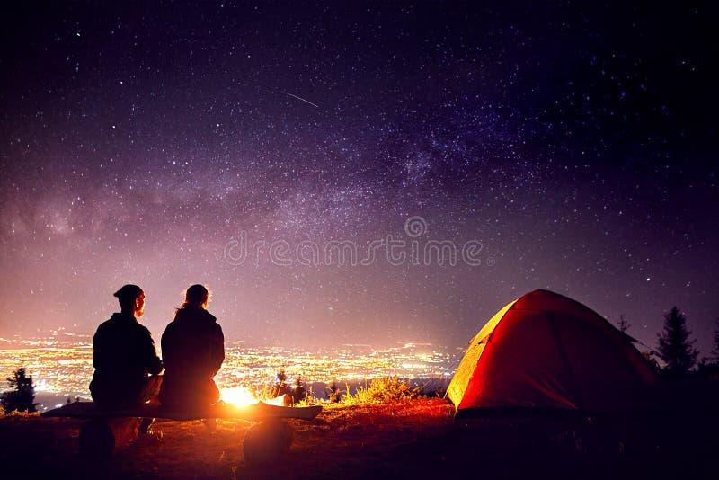 Les couples romantiques s'approchent du feu de camp au ciel étoilé photos libres de droits