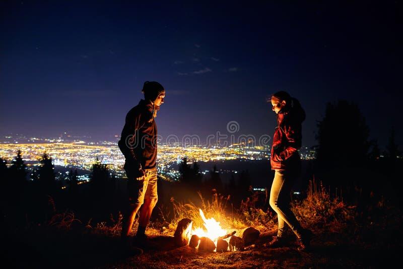 Les couples romantiques s'approchent du feu de camp la nuit étoilé photographie stock