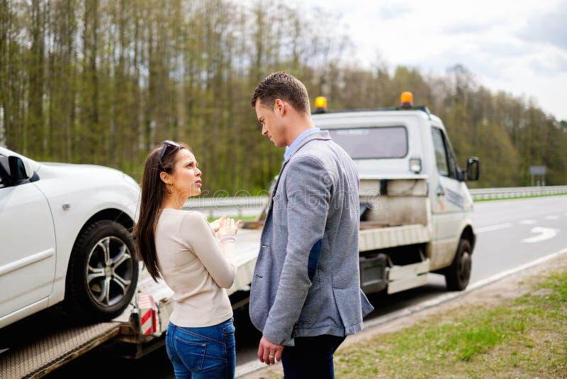 Les couples s'approchent de la voiture cassée sur un bord de la route photo libre de droits
