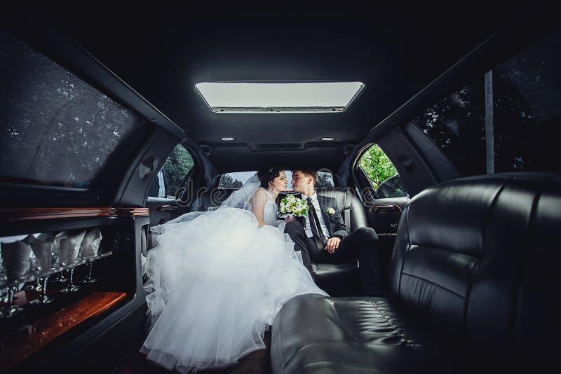 Les couples se reposant dans la limousine Portrait d'un beau jeune couple qui monte autour de la ville photos stock