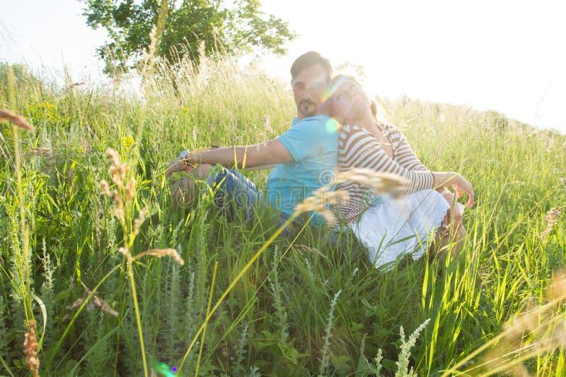 Les couples se reposant sur l'herbe verte brillent au soleil le rayon Homme et femme sur la terre dans l'herbe se regardant au-de image libre de droits