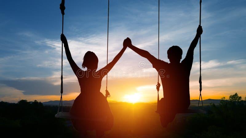 Les couples se reposent sur des oscillations et joignent des mains Sur le fond du s photo stock