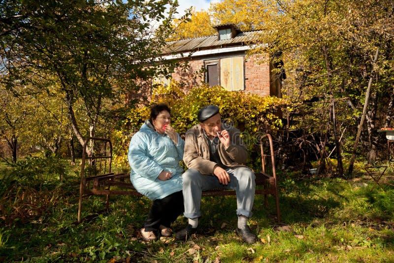 Les couples se reposent sur le vieux bâti rouillé dans le jardin automnal photographie stock