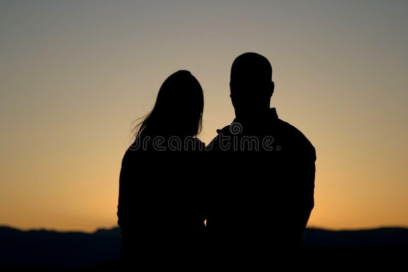 Les couples silhouettent au coucher du soleil photo stock