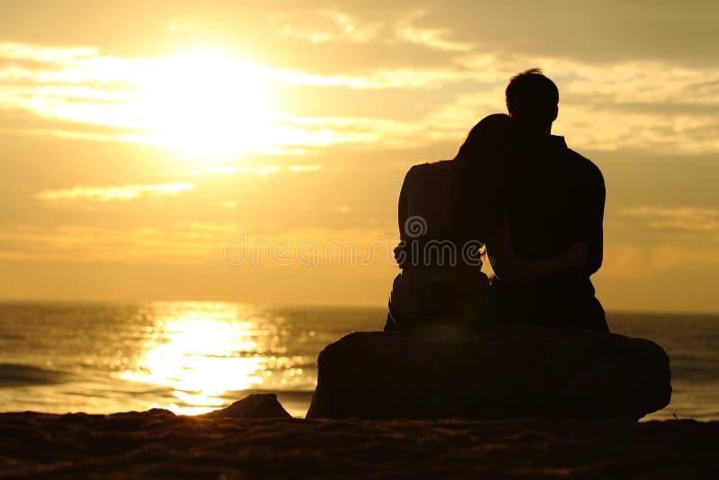 Les couples silhouettent le coucher du soleil de observation sur la plage photographie stock