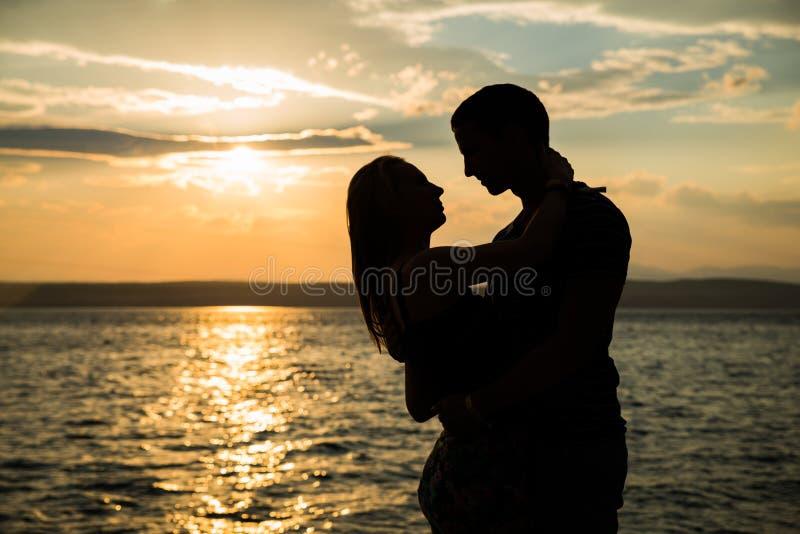 Les couples silhouettent sur la plage photos stock