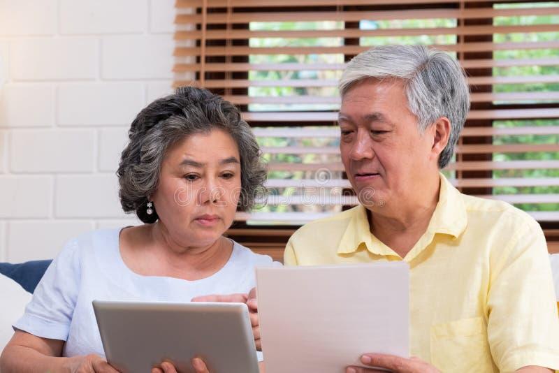 Les couples supérieurs asiatiques calculent le comprimé financier d'utilisation de retraite recherchant le document se reposant s photographie stock