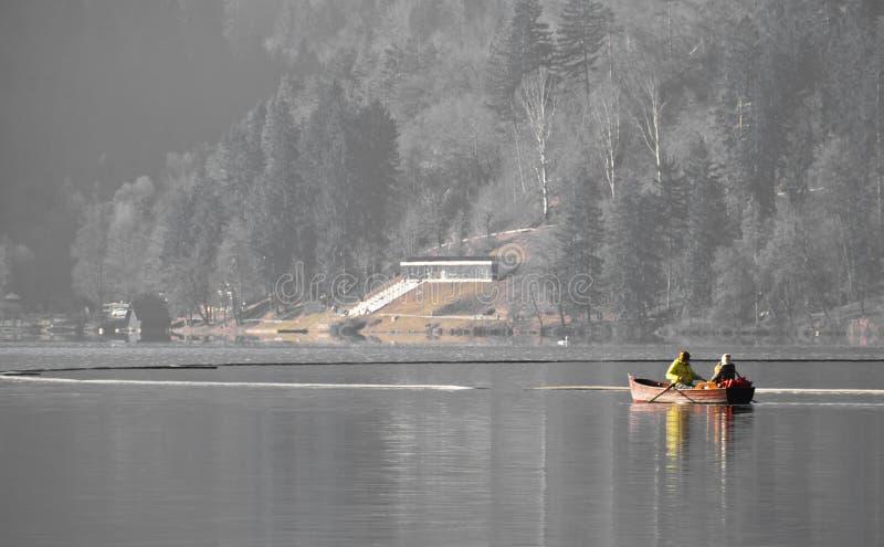 Les couples sur le bateau à rames de détente de voyage sur le lac ont saigné en hiver image libre de droits