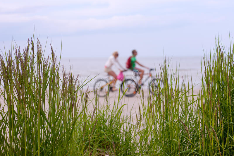 Les couples sur un vélo montent le long de la plage image libre de droits