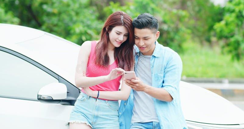 Les couples utilisent le téléphone avec la voiture images stock