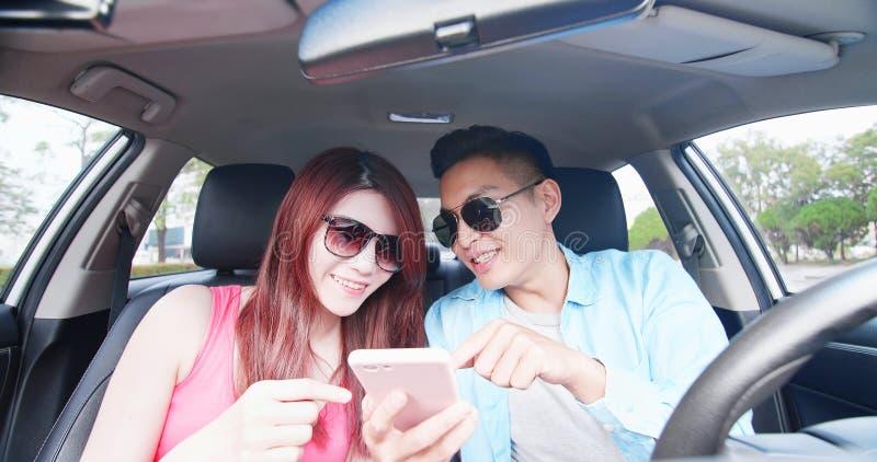 Les couples utilisent le téléphone dans la voiture photographie stock