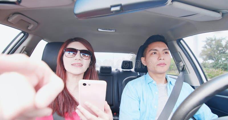 Les couples utilisent le téléphone dans la voiture photos stock
