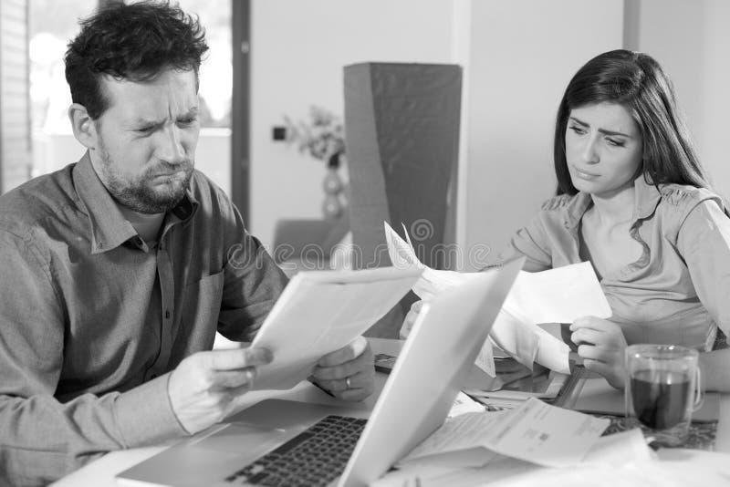Les couples vérifiant des factures ont à la maison inquiété noir et blanc malheureux photos libres de droits