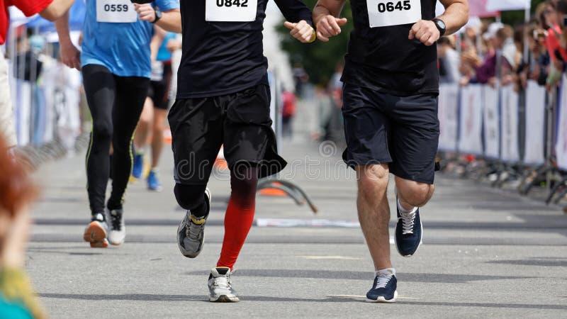 Les coureurs d'athlètes fonctionnent sur une voie de sports photo stock