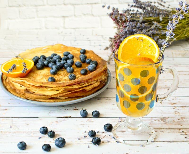 Les crêpes avec des myrtilles poussent des feuilles sur la limonade supérieure et orange d'agrume avec des bâtons de lavande Fich images stock