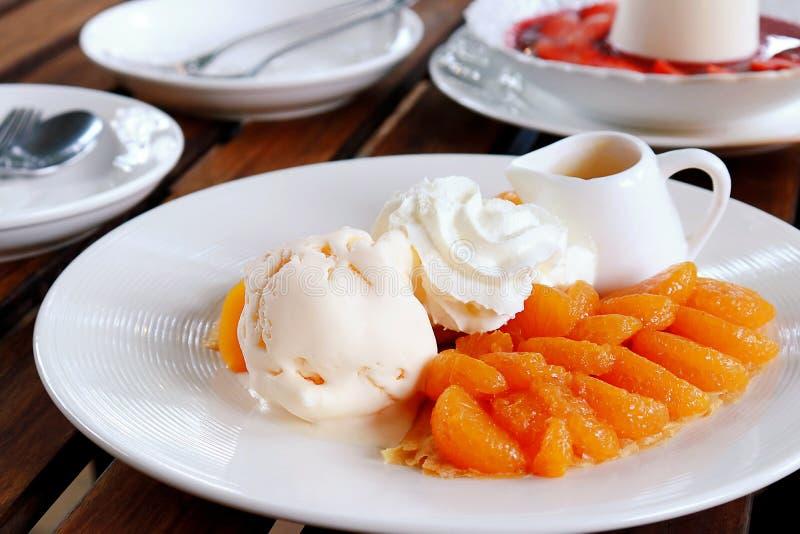 Les crêpes délicieuses avec l'orange, crème glacée, ont fouetté le sirop crème et orange du plat blanc image libre de droits