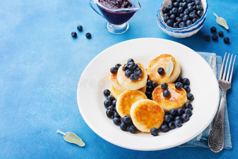 Les crêpes de fromage blanc ou les beignets de lait caillé ont décoré le miel et la myrtille dans le plat sur la table bleue Peti images libres de droits