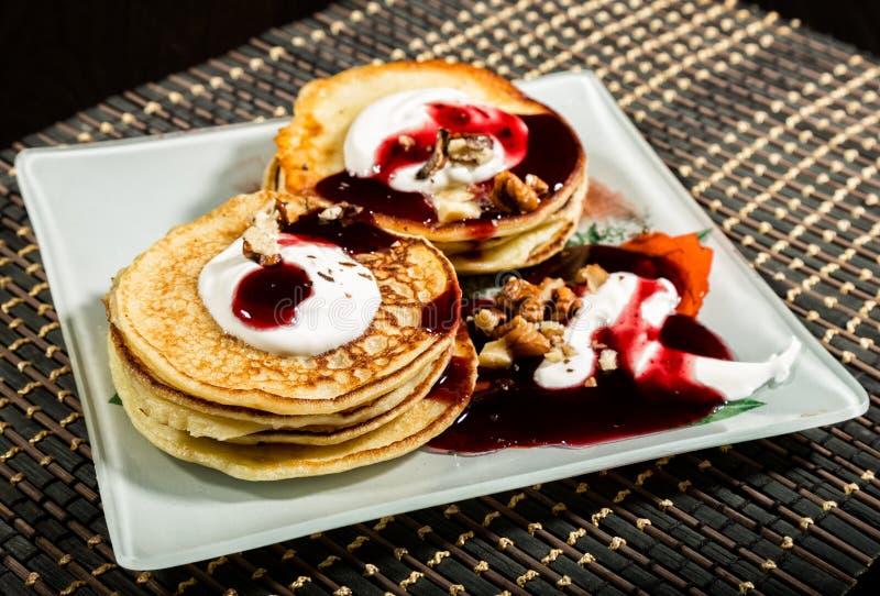 Les crêpes douces faites maison avec le fruit bloquent, crème sure d'un plat blanc Le petit déjeuner avec la pile a complété la c photos libres de droits