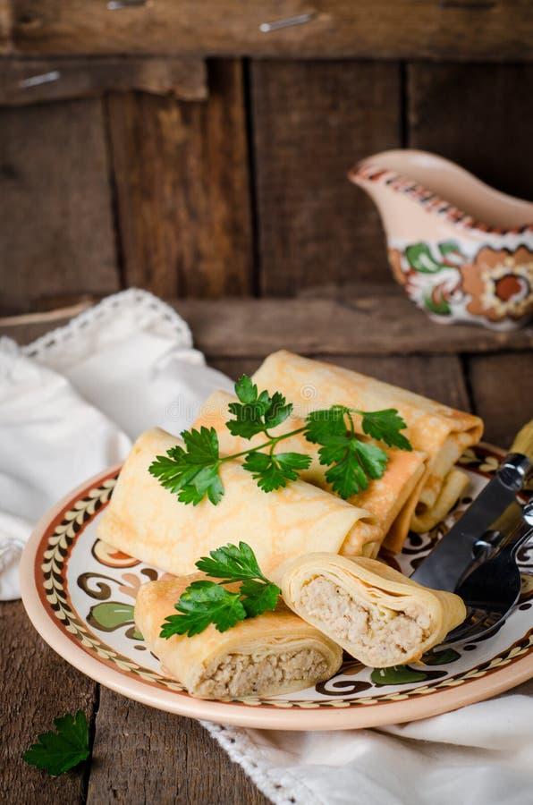 Les crêpes russes bourrées roule avec de la viande dans la cuvette traditionnelle d'argile sur le fond en bois Image modifiée la  images stock