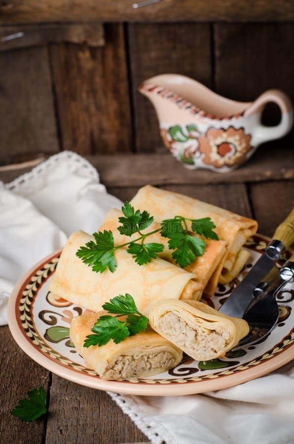 Les crêpes russes bourrées roule avec de la viande dans la cuvette traditionnelle d'argile sur le fond en bois Image modifiée la  photos stock