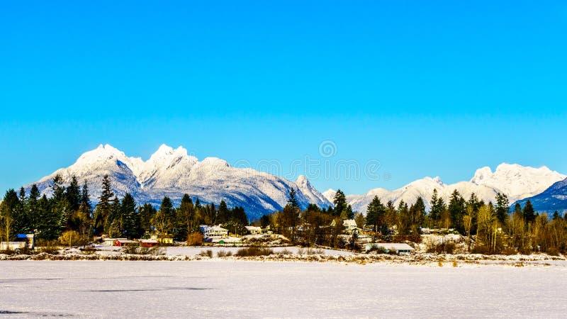 Les crêtes couvertes par neige des oreilles d'or montagne et du bâti Robie Reid derrière la ville du fort Langley dans Fraser Val photo stock
