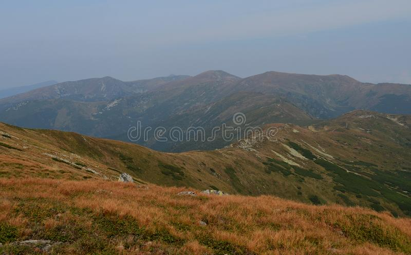 Les crêtes des montagnes carpathiennes Chaînes de montagne couvertes de forêts sous les nuages bleus photographie stock libre de droits