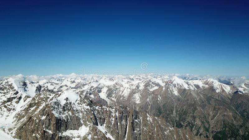 Les crêtes neigeuses des montagnes montent au-dessus du ciel bleu Les glaciers de la roche sont évidents photo stock