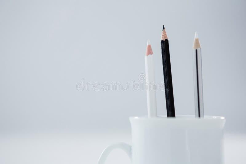 Les crayons colorés noirs et blancs ont maintenu dans la tasse sur le fond blanc image stock