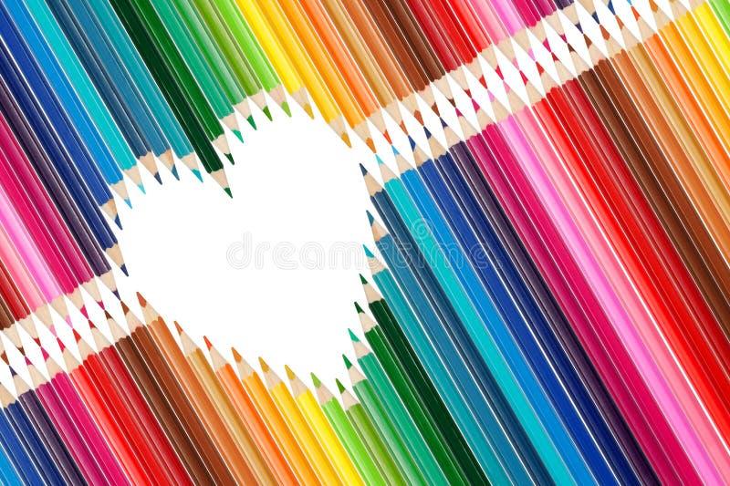 Les crayons colorés ont placé au milieu de la forme de coeur photo libre de droits