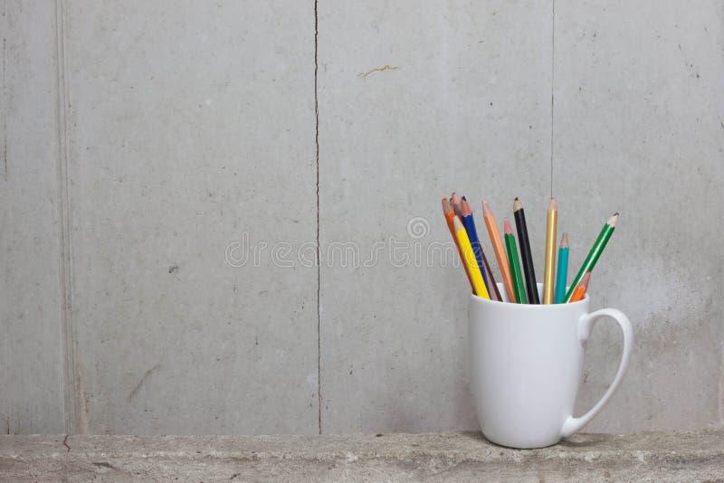 Les crayons de couleur cassés sur la tasse blanche s'étendent sur le ciment image stock