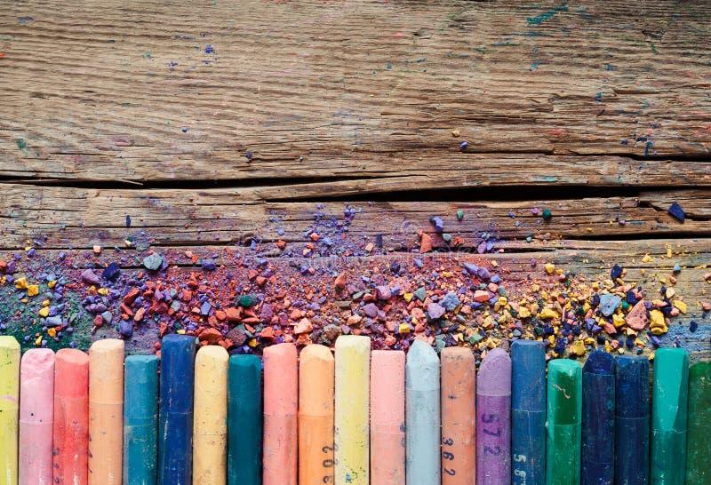 Les crayons et le colorant en pastel époussettent sur le fond en bois rustique photos libres de droits