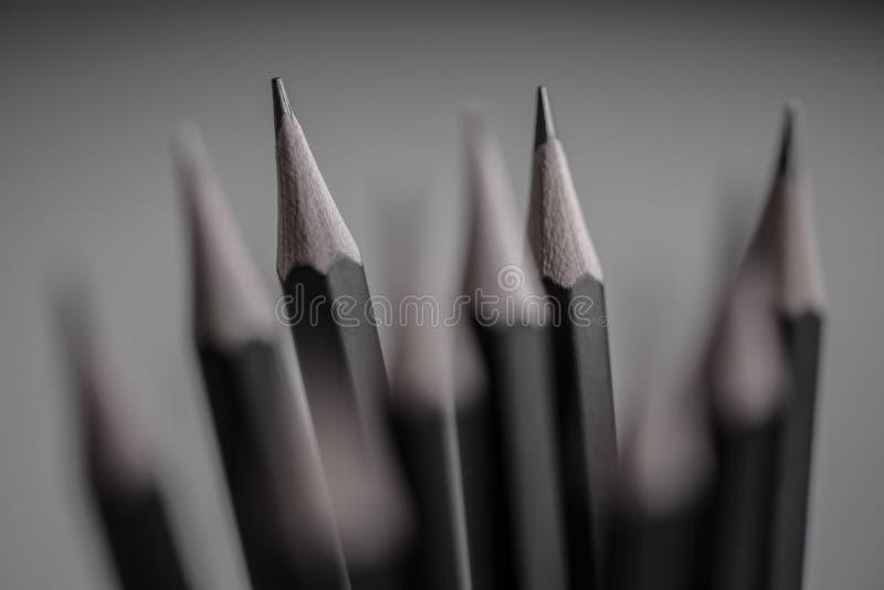 Les crayons noirs inclinent le plan rapproché avec davantage brouillé dans le backround photo libre de droits