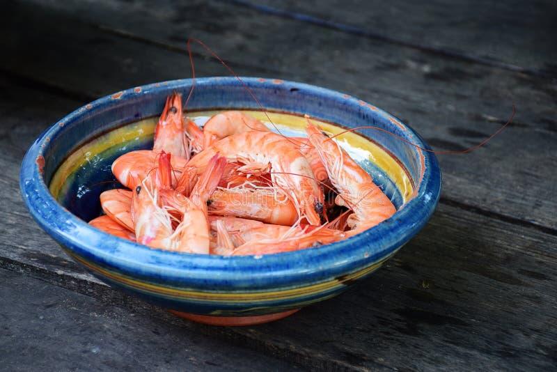 Les crevettes bouillies de tigre dans une poterie de terre roulent sur le bois foncé rustique photographie stock libre de droits
