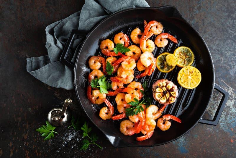 Les crevettes roses ont rôti sur la poêle de gril avec le citron et l'ail Crevettes grillées, crevettes roses Fruits de mer Vue s photo libre de droits