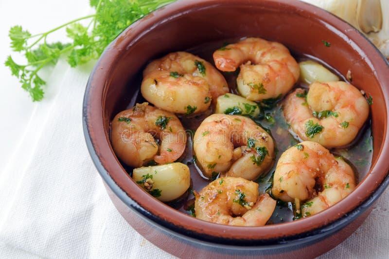 Les crevettes roses ou les crevettes avec l'ail et le persil en xérès sauce dans un t photographie stock