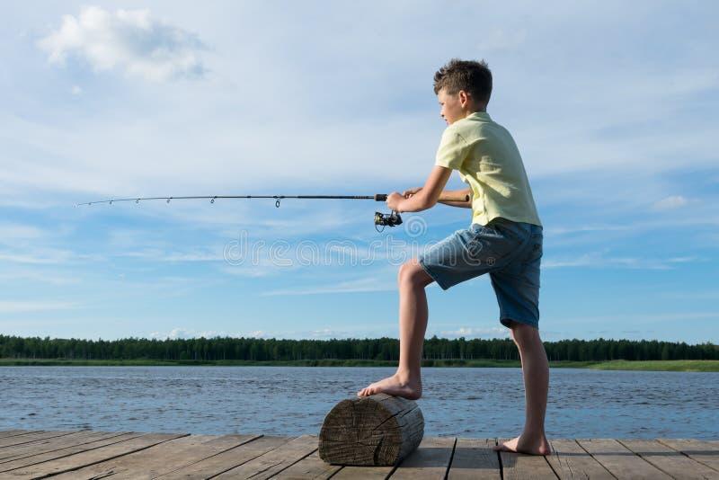 Les crochets de garçon pêchent avec une canne à pêche sur un lac dans la perspective d'un beau ciel, vue de côté images libres de droits