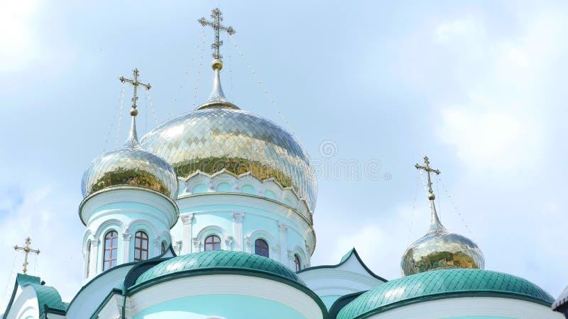Les croix orthodoxes orientales sur l'or couvre d'un dôme des coupoles contre le ciel nuageux bleu photo libre de droits