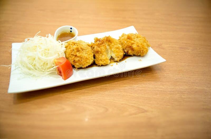 Les croquettes de fromage de pomme de terre, garniture est chou et service de tomate du plat blanc photographie stock