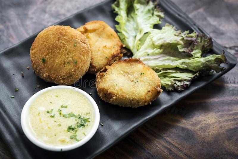 Les croquettes de poisson frites avec du beurre d'ail sauce le casse-croûte image libre de droits