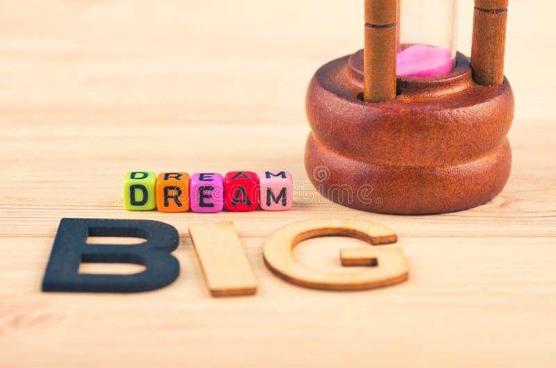 Les cubes colorés avec des mots RÊVENT GRAND sur le bureau en bois photographie stock libre de droits
