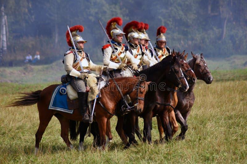 Les cuirassiers de Reenactors montent des chevaux à la reconstitution historique de bataille de Borodino en Russie images stock